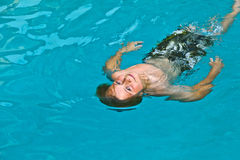 Boy enjoys swimming in the pool Royalty Free Stock Photo