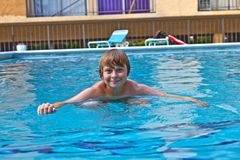 Boy enjoys swimming in the pool Stock Photo