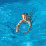 Boy enjoys swimming in the pool Stock Photos