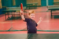 The boy is happy to win in table tennis stock images