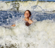 Boy enjoys the waves in the rough ocean Royalty Free Stock Images