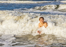 Boy enjoys the waves in the rough ocean Stock Photography