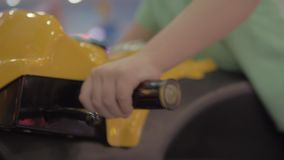 Boy entertaining with motorbike racing simulator. Close-up shot of a child driving motorcycle when playing racing simulator video game in amusement park stock footage
