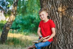 Boy enthusiastically reading a book in the Park . Boy reading a book in the Park . The concept of out-of-school education . Outdoor recreation stock images