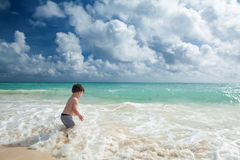 Boy enyojs summer day at the tropical beach. Stock Photo