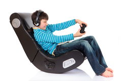 Boy in ergonomic chair. A studio view of a boy playing a video game while sitting in a large, comfortable ergonomic chair Royalty Free Stock Images