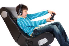 Boy in ergonomic chair. A studio view of a boy playing a video game while sitting in a large, comfortable ergonomic chair Royalty Free Stock Photos