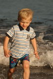 Boy is escaping from the sea. Small boy catching the last minutes of a day on the irish beach Royalty Free Stock Photo