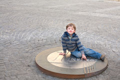 Boy and eurocoin Stock Images