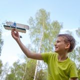 A boy of European appearance with an airplane against the sky with clouds. Bright emotions. Life style royalty free stock images