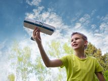 A boy of European appearance with an airplane against the sky with clouds. Bright emotions. Summer mood stock photos
