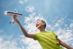 A boy of European appearance with an airplane against the sky with clouds. Bright emotions. Summer mood royalty free stock image