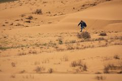 A boy of European appearance fun runs around the dunes. The boy is wearing blue jeans and a blue jacket. Sunny spring day. Bright royalty free stock photo