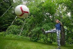 A boy of European appearance plays football. Bright emotion, flying ball royalty free stock images