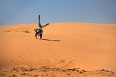 A boy of European appearance stands on his hands in the midst of the dunes. The teenager is wearing a blue jacket and blue jeans. royalty free stock images