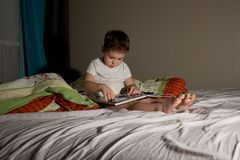Boy in the evening on the bed of the parents reading a book royalty free stock photos