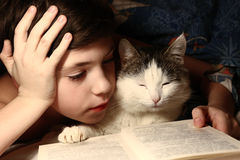 Boy evening read book with cat. Preteen handsome boy evening read book with cat in the bed before sleeping Royalty Free Stock Photography