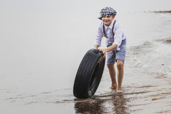 A boy in the evening at the tyre rolling Stock Photography
