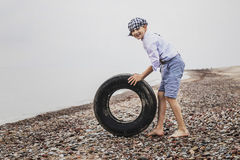 A boy in the evening at the tyre rolling Royalty Free Stock Photography