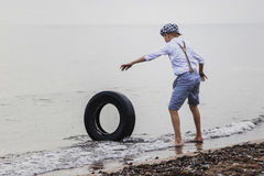 A boy in the evening at the tyre rolling Stock Image