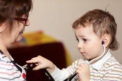 Boy examines grandmother using stethoscope Royalty Free Stock Photos