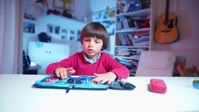 A boy examines a school pencil case, takes out a pencil. A boy in a red sweater sits at a table examines a school pencil case, takes out a pencil stock footage