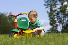 Boy examing tricycle Royalty Free Stock Image