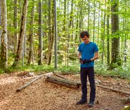 Boy examining the GPS device on trail. Boy reading a gps map on his mobile device in the forest Royalty Free Stock Image