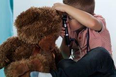 Boy examining teddy bear Stock Images
