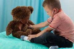 Boy examining teddy bear by stethoscope Stock Photos