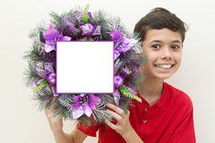 Boy excited while holding purple Christmas wreath. Stock Photography