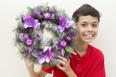 Boy excited while holding purple Christmas wreath. Stock Photos