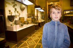 Boy at excursion in historical museum. Near exhibits of ancient relics in glass cases Stock Photography
