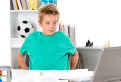 Boy with exercise book and PC on tesk Royalty Free Stock Photo