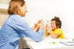 Boy Exercises Putting Fingers With Therapist Stock Image