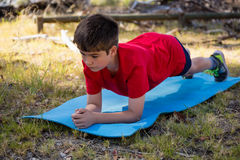 Boy exercising on exercise mat during obstacle course training Stock Photography