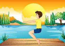 A boy exercising near the deep river Royalty Free Stock Images