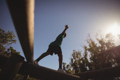 Boy exercising on obstacle during obstacle course stock photos
