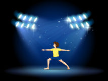 A boy exercising at the stage with spotlights Stock Photos