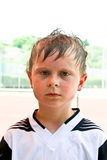 Boy with sweaty face and wet hair looks. Exhausted after soccer match stock images