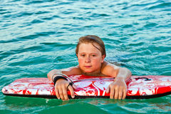 Boy exhausted from surfing Stock Image