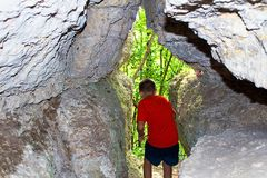 The boy exits the cave in the rock, the rear view. Warm summer, afternoon, evening Royalty Free Stock Photography