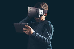 Boy experiencing virtual reality. On the black background Royalty Free Stock Photography