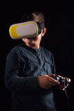 Boy experiencing virtual reality. Child experiencing virtual reality on the black Stock Image