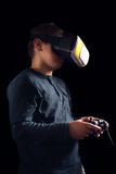 Boy experiencing virtual reality. Child experiencing virtual reality on the black Stock Photo