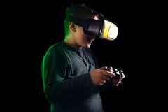 Boy experiencing virtual reality. Child experiencing virtual reality on the black Royalty Free Stock Photo