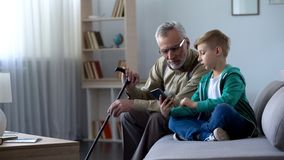 Boy explaining to grandpa how to use cell phone, simple technologies for old man. Stock photo stock image