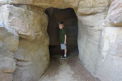 Boy Exploring Cave. Young boy of 8 years at entrance to Disneyland Tom Sawyer Island cave. A bit reluctant to enter the cave on his own. Facial expression says Royalty Free Stock Photography