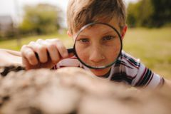 Boy exploring with magnifying glass at the park. Closeup of cute kid with magnifying glass outdoors. Boy exploring with magnifying glass at the park royalty free stock photography