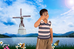 Boy exploring nature with magnifying glass Royalty Free Stock Photography